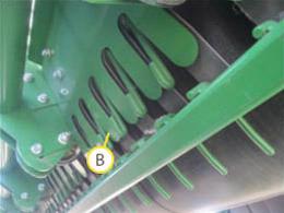 Os dedos de aço de bico de pato (B) não devem entrar em contato com as correias de prensa na parte inferior no rolo.