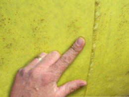 Os dedos curvados no bico de pato de tal modo que estão em contacto com a correia do fardo.