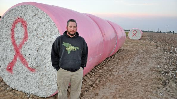 Jason Chandler with round cotton bales in pink plastic
